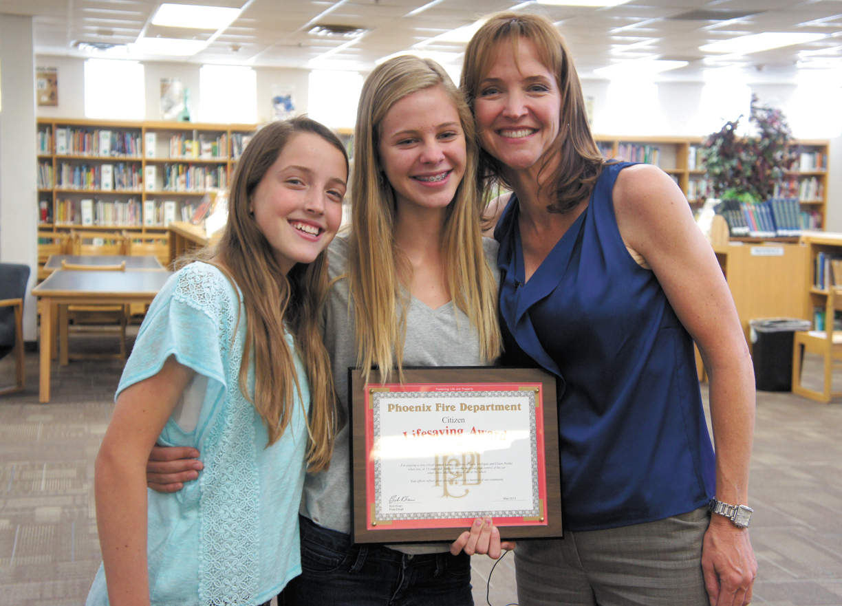 Brooke Gerlach, center, displays the plaque presented to her by the Phoenix Fire Department for potentially saving her own life as well as the lives of Susan Mulligan, right, and Susan's daughter, Claire Pischko, left (photo by Teri Carnicelli).