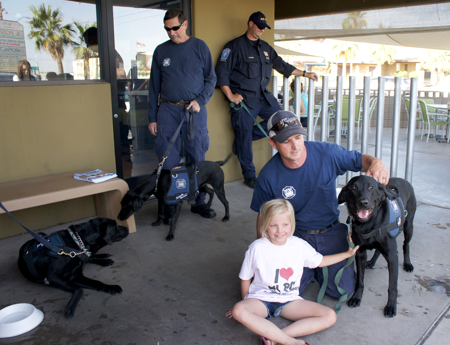 Teams from Arizona Search Dogs recently visited Scramble restaurant for a fundraising event. The breakfast-all-day eatery at 9832 N. 7th St. donated 15 percent of all sales on the night of May 29 to the nonprofit group, while search dogs and their handlers visited with restaurant patrons outside. Among them were, clockwise from left: Moose, who sniffs noses with new trainee Rainey with handler Don Peyton of the Phoenix Fire Department; Mike Rohme of the Phoenix Police Department with his dog, Ruger (out of frame); Hoss, with his handler Dana Medlin of the Phoenix Fire Department and Dana's 9-year-old daughter, Addie. Proceeds from the evening will be used toward paying for the training and care of two new search dogs: Free and Rainey. There are less than 20 search dogs currently in the organization, the majority of them being black Labrador retrievers. For more information, visit www.ArizonaSearchDog.org.