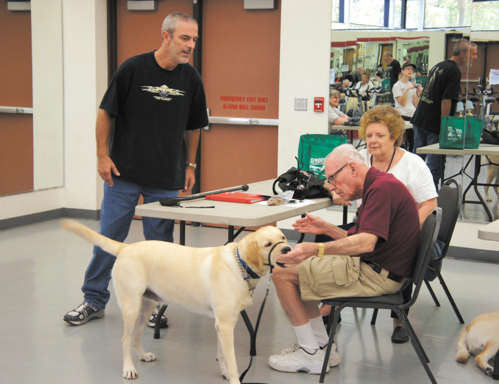 "Jake Willison, left, an instructor with Happy Tails Service Dogs, watches as student Robert Westfall commands his 3-year-old yellow Labrador retriever, Molly, to ""touch"" his hand, while Robert's wife, Dorothy, looks on. The ""touch"" command can be used to teach a dog to do everything from turning on a touch lamp to pushing open a door (photo by Teri Carnicelli)."