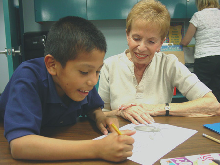 Volunteer tutor Paula Sherman works with Israel, a student at Madison Heights, as part of the OASIS tutoring program. The next volunteer orientation is set for Sept. 23-25 (submitted photo).