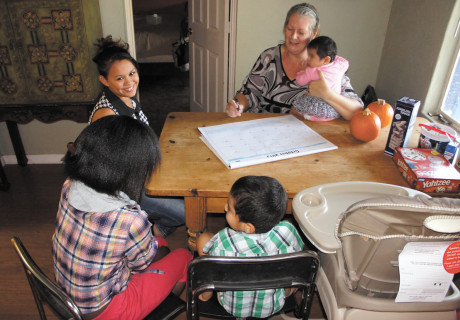 Adoptive and foster parent Michelle Harrington plans out the week's activities with her adopted daughter, Luz (left), and her three foster children (photo by Teri Carnicelli).
