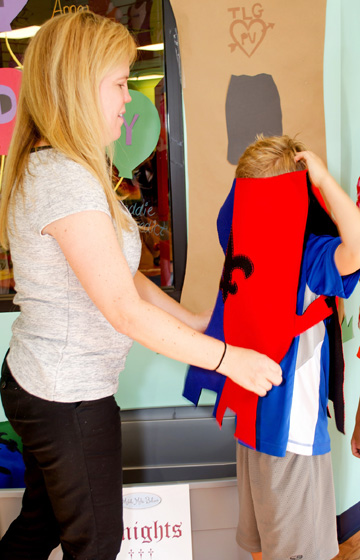 North Central resident Andrea Tyler Evans, owner of Mobile Make-Believe, helps a young customer on with his Knight outfit during a special theme party (photo by Bright Photography).