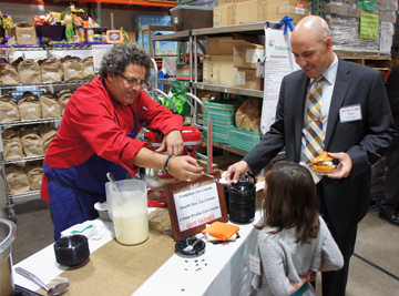 Local celebrity Chef Eddie Matney gives Reece Reichwald, 6, a taste of his homemade crème brule ice cream while dad Tim Reichwald looks on, during the Nov. 6 Taste of Desert Mission fundraising event (photo by Teri Carnicelli).