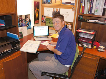 North Central youth Jeffrey Miller goes to an online high school in order to travel around the country to play competitive golf. His work station at home contains a laptop, books, and inspirational photos—and at least one familiar college logo (photo by Teri Carnicelli).