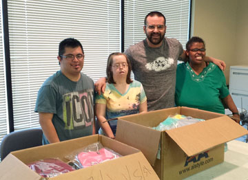 Robert Thornton, second from right, owner of Paper Clouds Apparel, gets help packaging up his T-shirts from special needs adults, from left: Antonio, Jennifer an Diamond. Last names are not used to protect their privacy (photo courtesy of Paper Clouds).