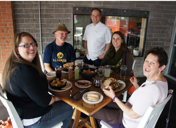Doug Robson, co-owner of Otro Café, visits with the Ballard family dining al fresco on the patio (clockwise from left): Marie, Greg, Anne and Maureen (photo by Teri Carnicelli).