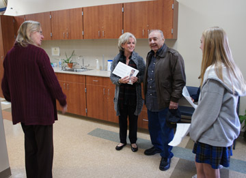 St. Francis Xavier School nurse Marie Heggestad, left, happily shows off her new nursing office to school visitors, Betsy Williams and Louis Reinhart, as well as SFX student Ana Alvarez, who was leading the woman and her father-in-law on a tour of the new school wing during Grandparents Day on Dec. 6 (photo by Teri Carnicelli).