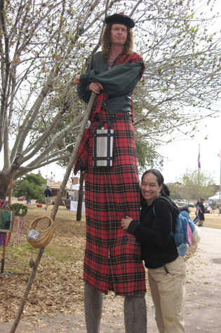 North Central resident Kezia Allen tries to cheer up a sour Scottish stilt walker with a hug during the annual Arizona Scottish Gathering & Highland Games (photo by Teri Carnicelli).