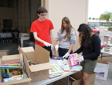 Sorting and labeling children's books donated to the Washington Elementary School District are members of the Sunnyslope High School Key Club, from left: Scott Kottmer, Ally Marshall and Denisse Roman (photo by Teri Carnicelli).