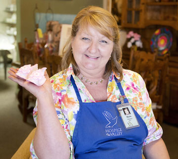 Maria D'Elia holds up a tiny pair of baby booties that she custom makes and donates for sale to the Hospice of the Valley White Dove Thrift Shoppe at 5035 N. 7th Ave., where she also volunteers (photo by Jaime Scowley, HOV).