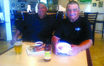 Chris Rideau, left, and his father, Charles, owners of Town Talk II Creole Style Bar-B-Q, show off some of the restaurant's top sellers, including the half-slab of pork ribs with dirty rice and Bubba beans, the Town Talk II red ale from Four Peaks Brewery, and the peach cobbler with vanilla ice cream, as well as their signature barbecue sauce, which can be bought at AJ's Fine Foods (photo by Patty Talahongva).