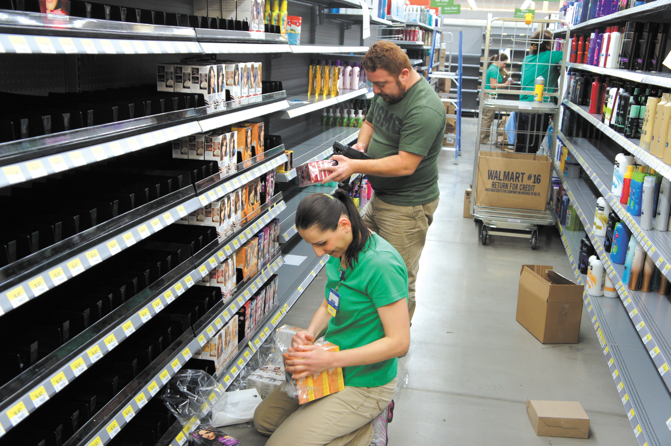 Walmart Neighborhood Market employees, including Hanaa Qiryaquos (left) and Salwin Korkies, stock the shelves in the hair care/beauty section in advance of the store's grand opening in Sunnyslope, set for June 11 (photo by Teri Carnicelli).