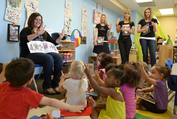 Enjoying a day of donating books and reading to children at the Phoenix Day early education center are members of Gallagher & Kennedy law firm's Professional Women's Group, including, from left: Laura Antonuccio (seated), Jennifer Cranston, Alana Hake and Jodi Bohr (photo by Patrick Corley).