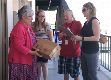 Lesli Stern, program manager at Valleylife (far right), and Valleylife member Chris deliver office supplies, printer ink and copy paper to Cathie Hanna McClellan, director of the Early Care and Education Center at Desert Christian Fellowship, and her administrative assistant, Amy Prigmore (submitted photo).