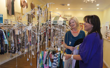 Poor Little Rich Girl sales associate Julie Sloan, left, helps customer Rebecca Mendoza browse through some of the upscale resale boutique's custom-made necklaces and pendants. The store, located in Sunbrite Corner at the northwest corner of 16th Street and Bethany Home Road, will be moving into a new, larger space under construction next door (photo by Teri Carnicelli).