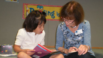 OASIS volunteer tutor Sheila Samalin reads a book with Arlet Vasquez, a second-grader at Madison Camelview Elementary (submitted photo).