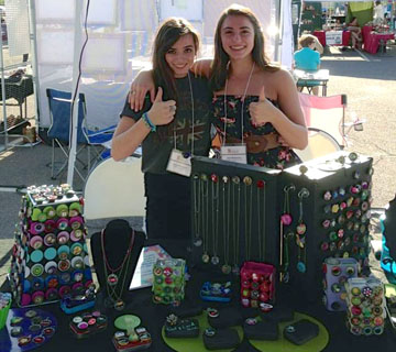 "Ileyna (left) and twin sister Flori Witenstein, both seniors at Sunnyslope High School show off some of the hundreds of ""Whoopies"" they've made and sold at the Sunnyslope Art Walk (on Facebook, Whoopies-Caps with a Cause). They decorate the bottle caps and then sell them to raise money and awareness of the need for everyone to be vaccinated against Pertussis, also known as whooping cough—which they both came down with in the summer of 2008 (submitted photo)."