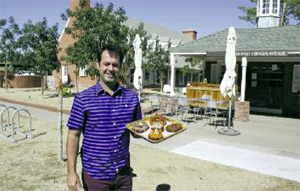 Brad Moore holds up a tray of doughnuts now available at his new business, Rollover Doughnuts. He's standing in the courtyard he shares with the owners of Oven + Vine restaurant. The red brick buildings once housed a dentist's home and office (photo by Patty Talahongva).