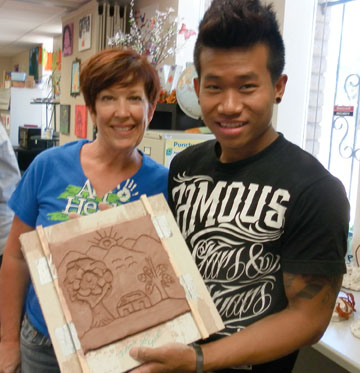 "Elizabeth ""Libby"" Noble, professional artist and volunteer mentor with Free Arts of Arizona, and Bei Chhasa, a refugee unaccompanied minor from Burma, admire the ceramic tile he created for a new mural on the wall at The Refuge café and wine bar (submitted photo)."