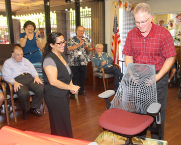 Stewart Hall, a service technician with Goodmans Interior Structures, surprises Alicia Gonzales, a recreation therapist at the Foundation for Senior Living, with a brand new chair as part of Goodmans' Chair Reaction program, celebrating the company's 60th anniversary (submitted photo).