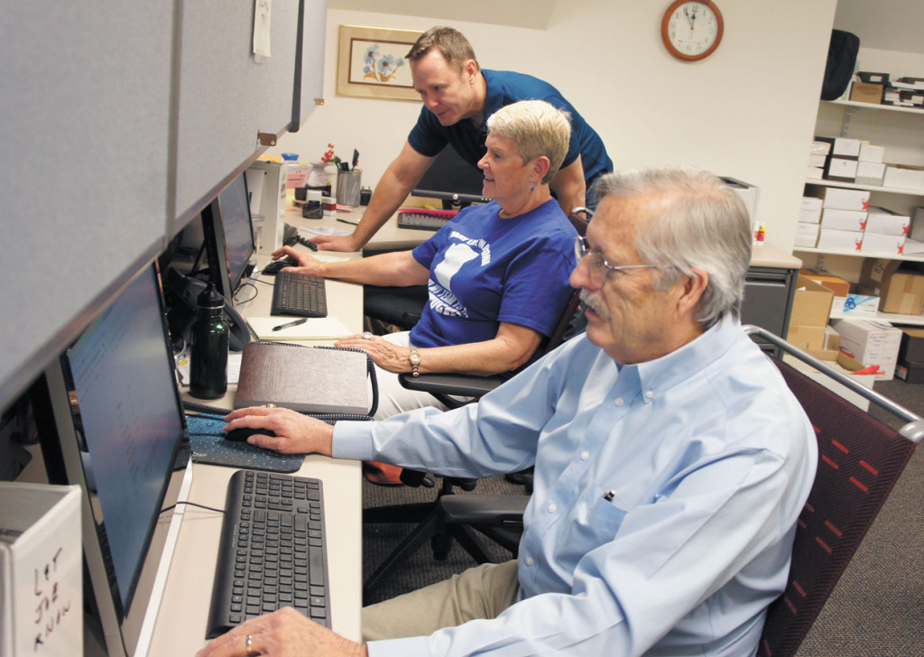 """ABC15 reporter Joe Ducey, back, discusses a consumer complaint with Charlotte Barnes, who along with Jim Cederstrom volunteers on Fridays answering e-mails and voicemails that come in for the """"Let Joe Know"""" consumer affairs program (photo by Teri Carnicelli)."""