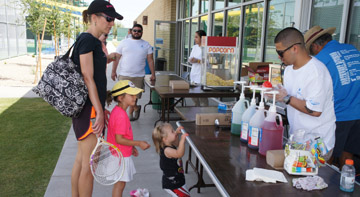 Eighteen-month-old Lea Faurel excitedly waits for Alex Gonzales of the Washington Activity Center to finish making her snow cone, while big sister Sydney, 5, patiently waits her turn and mom Lucile keeps a watchful eye. The family was enjoying the April 11 re-opening celebration of the Phoenix Tennis Center (photo by Teri Carnicelli).