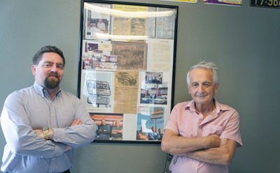 Dan Kingston, left, recently purchased Prentice Garage from Mitch Dehelean, right, who owned the auto repair shop for more than 20 years. On the wall of the revamped lobby is a framed history of the shop, which first opened in 1932 and is the only auto repair and service business in Phoenix to have operated continuously for more than 80 years (photo by Teri Carnicelli).