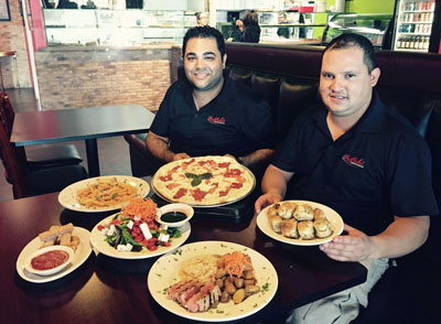 Nathan Uveydo, owner of La Bella Pizzeria and Restaurant, and manager Daniel Herrera show off a plethora of dishes they serve to an ever-growing customer base. Pictured are the Margarita pizza, Penne A La Vodka, Garlic Knots, Mozzarella Sticks, Grilled Tuna and the Insalata Bella (photo by Patty Talahongva).