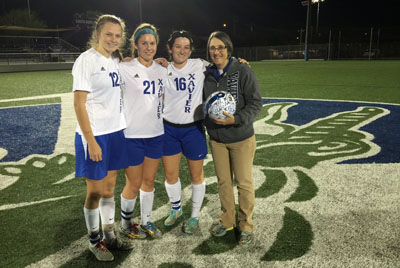 Xavier senior soccer players Kelly Harris, Amanda Lane and Kendall Ward present Gators athletic trainer Laurie White with an autographed ball at halftime of a match against Mountain Pointe last season (submitted photo).