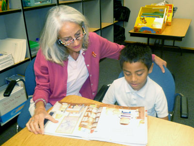 OASIS volunteer tutor Maggie Kraft works with student Erik Bautista on his reading skills (submitted photo).