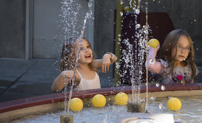 Two girls beat the heat by enjoying the water play area in the interior courtyard at the Arizona Science Center, which is offering free general admission Sept. 19-20 (photo by Alexis Macklin).