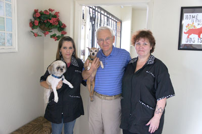 Gabor Vajda, center, owner of the new ServePets multi-service pet facility, says that your canine companions will be treated like family there. Pictured with him are groomer Jennifer Stiner, left, and her Shih Tzu, Weedo; groomer Tina Hemby; and Prissy, one of the two staff dogs at the North Central News (photo by Teri Carnicelli).