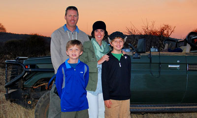 Enjoying a spectacular sunset at the Madikwe Game Reserve in South Africa are the globe-trotting Simmons family, clockwise from top left: dad Jeremy, mom Carrie, and sons Nathan and Seamus (photo courtesy of Travel With Kids).