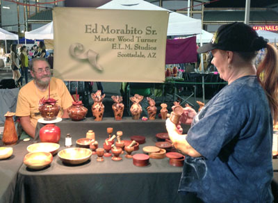 Kathleen Freedman chats with Master Wood Turner Ed Morabito Sr. of E.L.M. Studios during last fall's Sunnyslope Art Walk. Morabito, who teaches classes at the nonprofit S.E.E.D.S. for Autism, is a regular exhibitor at the twice-yearly art event in Central Phoenix (photo by Teri Carnicelli).