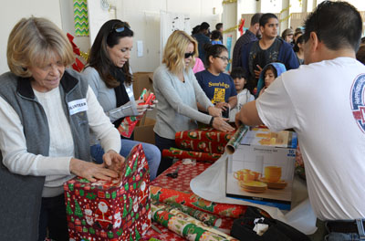 "Volunteers help wrap presents selected by children, for their parents, from the Winder Wonderland ""shopping"" area, hosted by Phoenix Rescue Mission each year for poor and homeless families (photo courtesy of Phoenix Rescue Mission)."