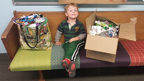 Caleb Camp, 3, a student at Cross Roads Preschool and Kindergarten, shows off some of his family's recyclables that are being brought in to the new recycling collection bins at the school (photo courtesy of Melisa Camp).