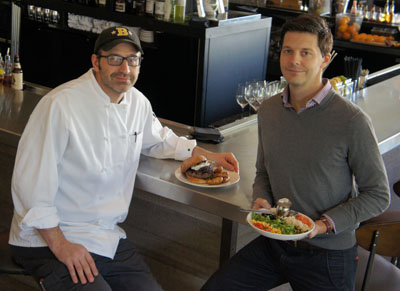 Bernie Kantak, left, chef and partner with The Gladly, and Andrew Fritz, partner and CEO, show off two of the eatery's most popular items. Kantak is holding The Wagyu Burger, featuring bacon-onion marmalade, Point Reyes blue cheese and arugula on a potato bun, accompanied by fried onion ash fingerlings with a garlic-aioli dipping sauce. Fritz offers up a signature dish first developed at sister eatery, Citizen Public House: The Original Chopped Salad, which has a combination of Israeli couscous, sweet dried corn, smoked salmon, asiago, pepitas, tomatoes, currants and arugula with a basil-ranch dressing (photo by Teri Carnicelli).