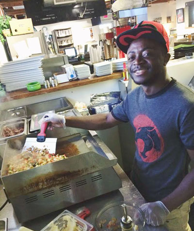 Rodrigue Wasanj, a 20­year­old refugee from the Democratic Republic of Congo who immigrated to Arizona in 2011, works as a cook at The Refuge Café, a social enterprise of Catholic Charities (photo courtesy of The Refuge).