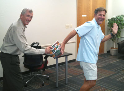 """Rather than a baton, Scott Hanson hands off his new book—""""Who is Gym?""""—to Tom Flood, who begins his sixth season as Grand Canyon University's head men's and women's track and field coach in 2016 (photo courtesy of HMA Public Relations)."""