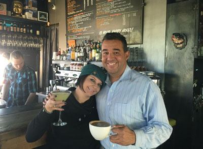 Rebecca Golden and one of her many regulars, Carlos Arboleda, show off two of their favorite drinks: for her, a Mint Lemondrop Martini, and for him, his regular cup of mocha. 32 Shea is both cafe and bistro depending on the time of day (photo by Patty Talahongva).