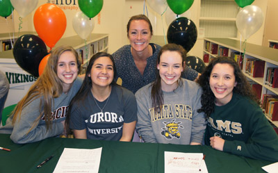 Sunnsylope High School Volleyball Coach Amber LeTarte, who was named the Division 1 Coach of the Year for 2015, congratulates her student athletes on their future college careers, from left: Skyler Wine, Sarah Marinez, Emma Wright, and Katie Oleksak (photo by Teri Carnicelli).
