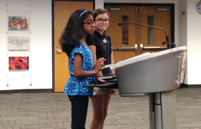 Amutha Rajasundaram, left, and Sally Fielder, both fourth graders at Madison Heights, speak to the Madison Elementary District Governing Board at its April 19 meeting about the health benefits of being active at recess as well as the opportunity to socialize with friends, which they can't do in the classroom without risking getting in trouble (photo by Teri Carnicelli).