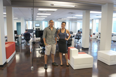 Odeen Domingo and wife Jenny Poon, co-owners of CO-HOOTS, stand in one of the large open shared working areas available at their new location, inside a 1960s midcentury modern office building at 221 E. Indianola Ave. The unique building is one of the few original structures raised up on stilts that remain in the Central Phoenix area (photo by Teri Carnicelli).