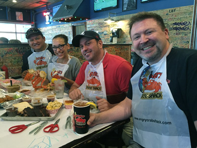 Owners Dan Sevilla, his wife Autum Perry-Sevilla and Andrew Diamond, along with Derek Still, general manager of The Angry Crab Shack, prepare to dive into a plethora of seafood and barbecue. The bibs are part of the dress code at the restaurant (photo by Patty Talahongva).