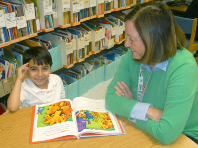 OASIS volunteer tutor Pat McKenna works with student Juan Luna on his reading skills (submitted photo).
