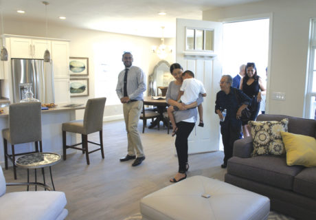Zahid Ali enters his brand new home in Sunnyslope on July 26 followed by wife, Stephanie (with son Noé), and various guests and dignitaries. The home, manufactured by Champion Home Builders in Chandler, was donated to the Ali family by Rebuilding Together Valley of the Sun and NextGen Home. It was fully furnished thanks to Bassett Furniture (photo by Teri Carnicelli).