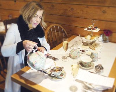 "Manchester, England-born Grace Unger, co-owner of Phoenix's Tuck Shop, enjoys one of the eatery's Saturday afternoon High Tea services, which includes tea served in the appropriately named ""Gracie"" China pattern, a selection of finger sandwiches and pastries, and an optional glass of champagne (submitted photo)."