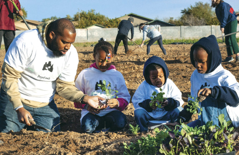 Volunteer Isaiah Norris works in a garden with his children (from left) Anaya, Nehemiah and Josiah as part of a Project Roots, Inc. project. Former Phoenix Mercury player Bridget Pettis started Project Roots, which grows and provides fruits and vegetables, as well as soup with the vegetables, to people in need (photo by Samantha Talavera).