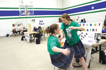 Talia Novak, on the left, a senior this school year, and Katie Harris, also a senior at Xavier College Preparatory demonstrate a centrifugal force activity during last year's Girls Have IT Day (GHITD) (photo by Dominique Paplaczyk).