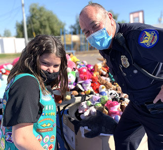 Shelby Shearer, 11, a fifth-grader at Phoenix Christian Preparatory, has been collecting stuffed animals to donate to traumatized children the Phoenix Police Department encounters since she was 3 years old. She is pictured here with Phoenix Police Officer Aaron Stevens (photo by Lisa Blake).